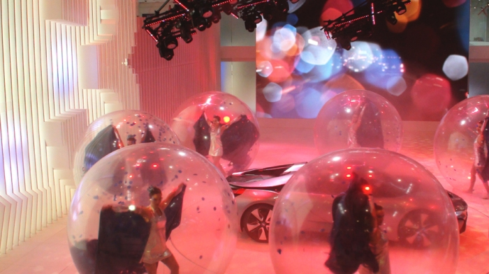 Dancers in transparent plastic bubbles.