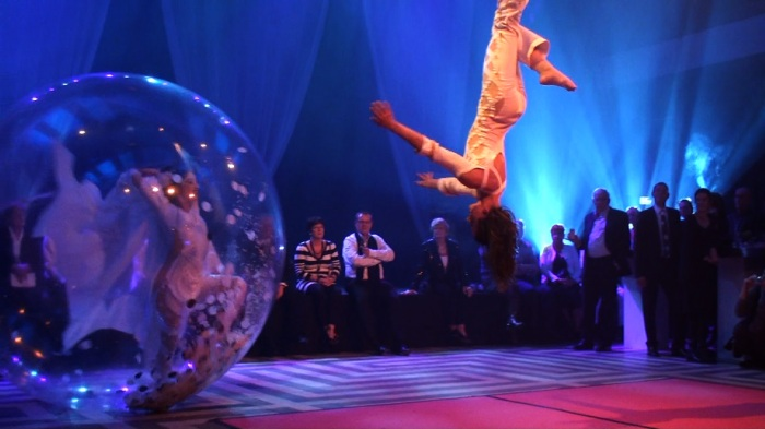 a dancer in a plastic ball playing, dancing with a trapezes acrobat.